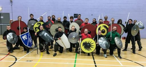 The Academy of Historical Fencing posing with mixed weapons and shields.
