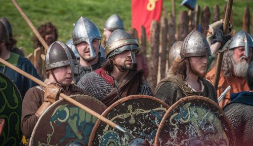 Vikings lined up with shields and weapons.