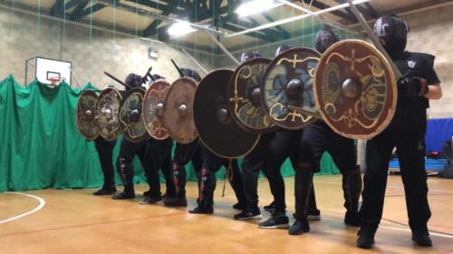 Academy of Steel members lined up in a shield wall with viking shields.